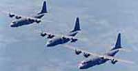Three C-130J Hercules aircraft flying in formation.